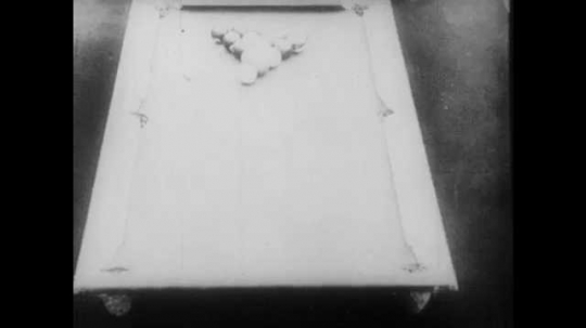 1910s: A pool rack breaks. The balls move around the table and return to their original formation. The crowd congratulates the man who took the shot. A second man steps up to the table to take a shot.