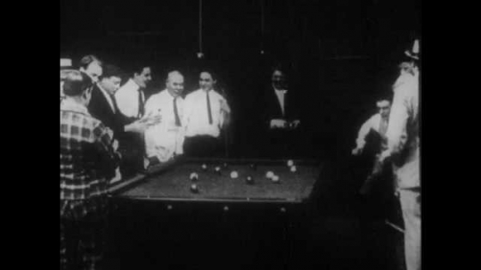 1910s: A man dumps a handful of pool balls on the table, disrupting the game. The crowd chastises him and resets the rack. His competitor breaks the rack and sinks every ball.