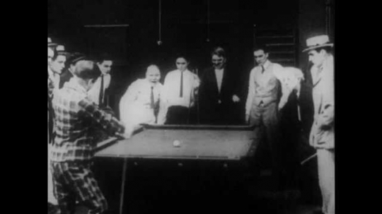 1910s: A crowd celebrates at a pool hall. Intertitle reads,
