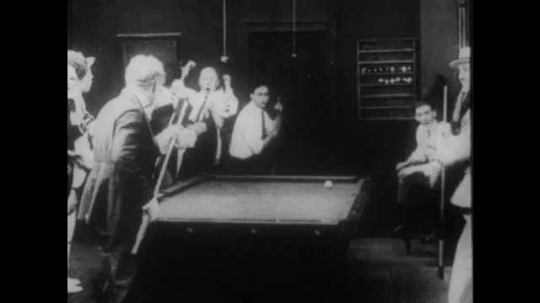 1910s: A crowd congratulates a man for a good shot at a pool hall. The man and his competitor fight and hit each other with pool cues. The crowd laughs.