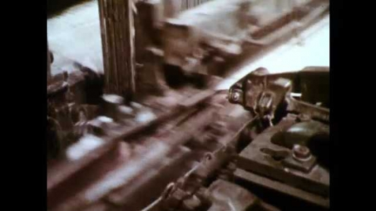 1960s: Cotton loom in motion, moving up and down, back and forth. Detail of cotton product in loom. Man working on bolt of fabric in textile plant.