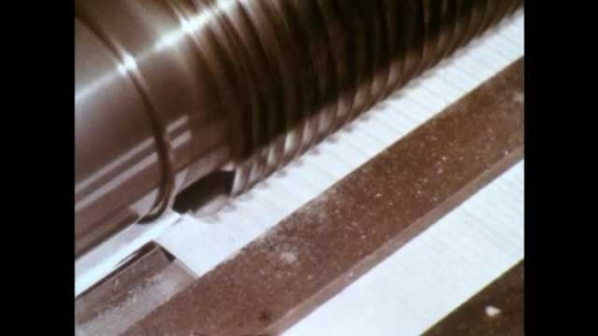 1960s: Metal cylinder with blades cuts fabric. Gears and belts in motion. Wheeled device measures length of fabric. Metal rods move back and forth. Length of ribbed cloth gently folded over self.