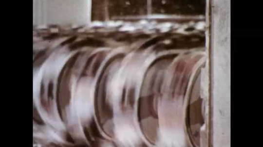 1960s: Machine belts in motion. Machine-brushes brush fabric. Metal cylinder feeds fabric into machine. Fabric moves through machine, folds onto ground. White fabric rolled by machine.