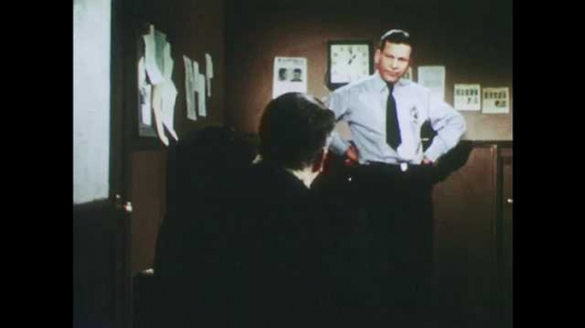 1950s: man in overcoat rises from sofa, talks, argues, points and walks to man with necktie and badge in police station with wanted posters and fingerprint cards on wall.