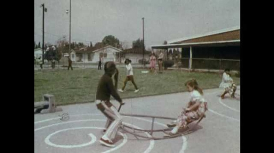1970s: UNITED STATES: children run to teacher in playground. Children sit on floor around teacher and policeman. Policeman crouches on ground