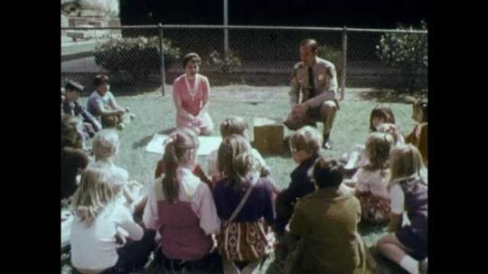 1970s: UNITED STATES: children sit around teacher and policeman in school yard. Lady speaks. Man kneels on ground. Policeman shows puppet to children