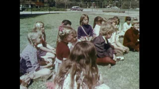 1970s: UNITED STATES: Children sit on grass. Close up of boy's face. Toy bear plays drums. Lady holds up stranger danger sign