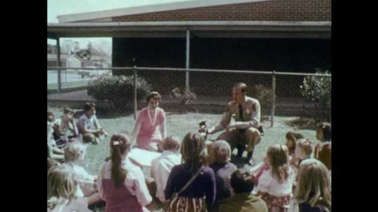 1970s: UNITED STATES: policeman speaks to students at school. Students gather around policeman. Bell rings on wall. Bikes in school yard