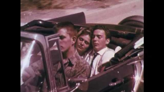 1960s: Couples driving in car, zoom out to car on road. Hand gives out pills from tissue, zoom out to boy distributing pills.