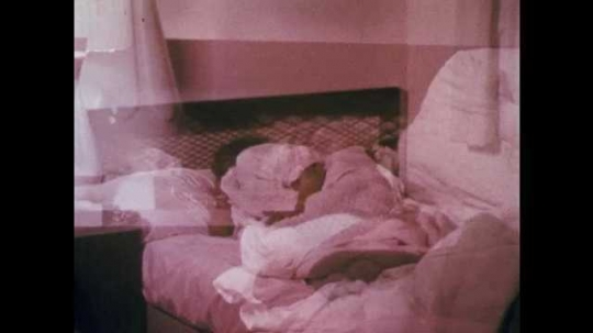 1960s: Zoom in on girl sleeping in bed. Girl in car, view of sidewalk through window, man arrested in background, car drives away. Girl approaches door.