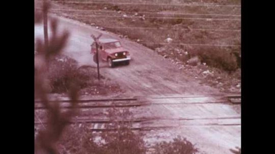 1970s: Jeep drives up to railroad tracks. Cartoon man turns crank on antique car, drinks from flask, gets car started, gets in and drives away.