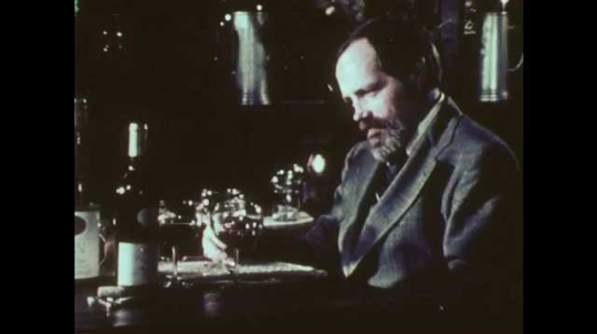 1970s: Man sits at table, swirls wine around in glass, holds glass up, looks at wine, sniffs wine, sips wine, sets glass down. Man looks thinks, talks.