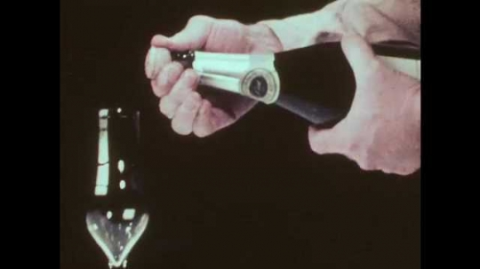 1970s: Man pops cork from champagne bottle, champagne explodes out of bottle, drips.