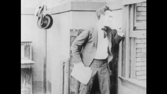 1910s: Women run around trees. Man leans against window and rips papers. Coworker taps boss on shoulder. Boss shakes head and speaks. Text placard. Boss reprimands man and yanks him across room.