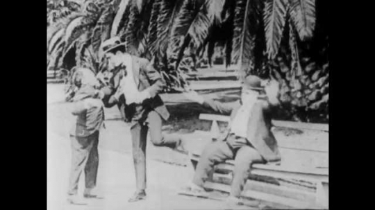 1910s: Man kicks man over bench. Man picks up small man and carries him. Couple sit on park bench. Man shoves woman away. Man dumps man in trash can. Man smacks man in back of head. Couple embrace.