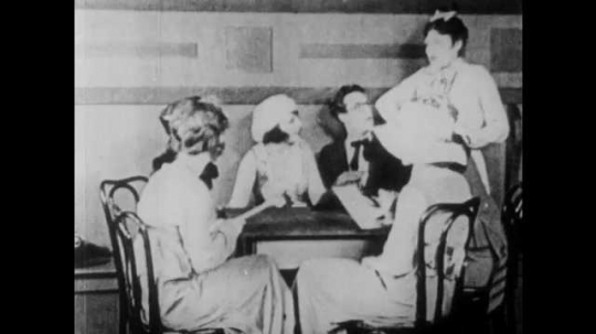 1910s: Man stands up from bush. Waitress hands bill to man. Man covers eye and looks at bill. Man steals handkerchief from couple and tucks it in pants.