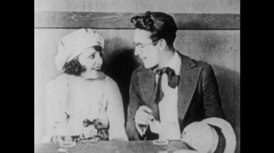 1910s: Waitress hands bill to couple in booth. Man from couple protests. Man and woman smile and eat ice cream. Man leaves table. Man attempts to leave diner but cook blocks him.