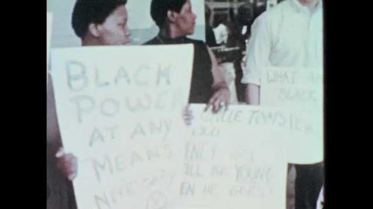 1960s: People stand outside, hold protest signs. Men sit at table, talk into microphones.