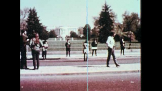 1960s: People stand around outside the White House. People march in the street. People throw rocks. Police in riot gear clash with protesters.