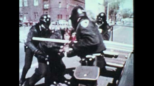 1960s: Police help injured man into car. Soldiers fight with civilian, restrain man, carry him away.