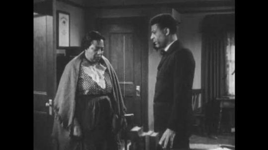 1940s: Woman in shawl angrily responds to man. Woman leaves office. Secretary enters office and hands man  a letter. Secretary speaks to man at desk. Man reads letter.