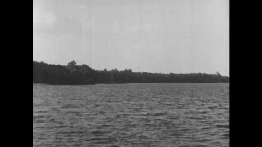 1940s: The James River. Wind fills sail on boat. Wooded shoreline of river. Sails fall as wind dies. Shallow water with protruding rocks.