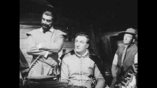 1950s: UNITED STATES: men listen to gentleman speak in tavern. Man folds arms. Mariners listen to talk in tavern.