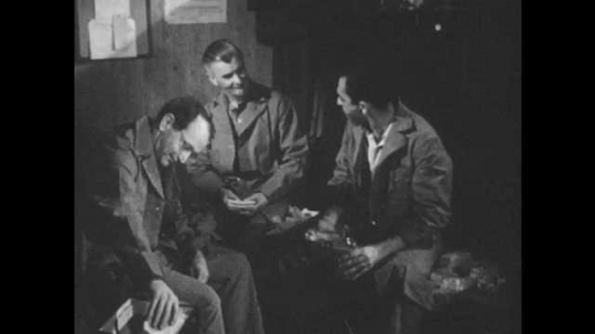1950s: Men sit on benches in break room and talk over lunch. Man looks up and speaks.