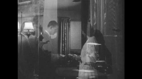 1950s: Man folds newspaper and answers telephone. Doctor speaks into phone. Man responds and hangs up phone. Man talks to self and walks away.
