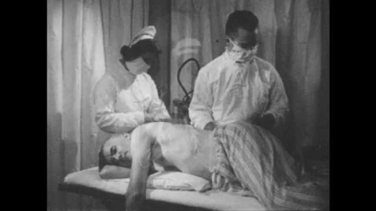 1950s: Patient lies on hospital bed while nurse and doctor prepare instruments. Doctor places cloth over mans back and prepares needle. Nurse rolls up sleeve of man and swabs arm. Nurse and man talk.
