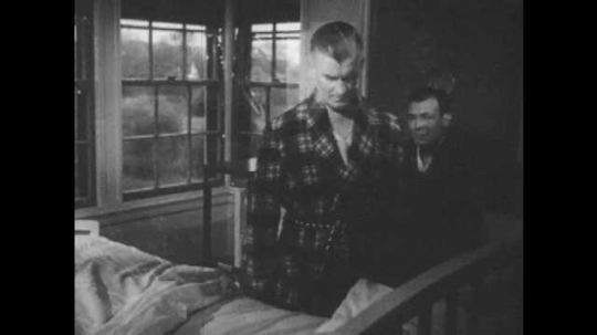 1950s: Man walks back and forth between beds in hospital room. Man sits on bed and watches fellow patient and talks. Men walk on sidewalk. Man sits on bench and poses for photo.