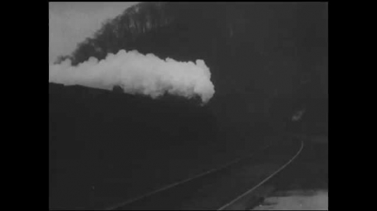 1930s: Train, billowing smoke from locomotive, comes around bend on tracks. Sign says, Hazard KY. Train going down tracks.