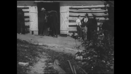 1930s: People stand in front of barn stables, with horse. Title card. Log cabin on hillside. People walk down path to cabin, carrying luggage.