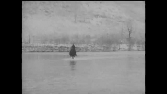 1930s: Woman riding horse across river. Title card. Two people sitting in front of fire in fireplace. Woman tends fire. Two people in front of fireplace. Woman rides horse across river.