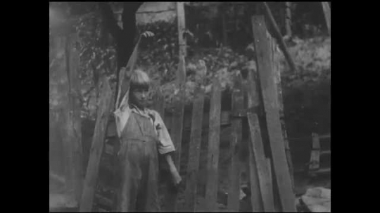 1930s: UNITED STATES: boy stays home. Boy waves at parents from gate of house. Cow in yard. Family go to hospital by mule.