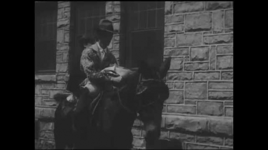 1930s: UNITED STATES: lady and man on horse arrive at hospital. Nurses come out to meet patients