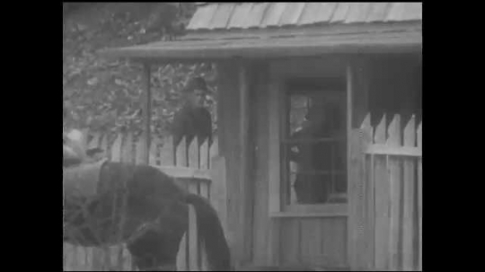 1930s: UNITED STATES: nurse mounts horse by wooden hut. Boy rides to village for help.