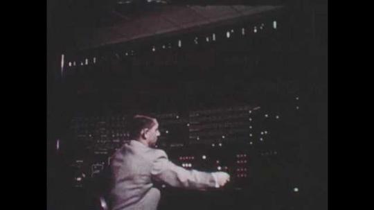 1950s: UNITED STATES: man operates machine. Hand presses switches on machine. Machine calculates numbers