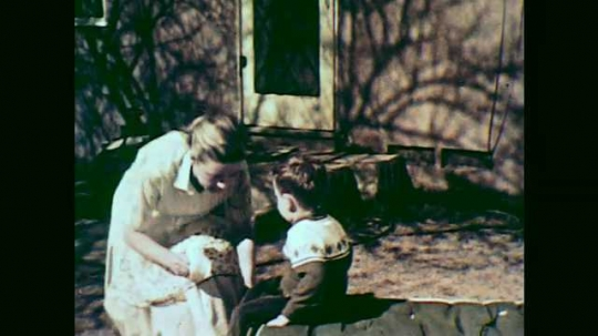 1950s: boy in sweater sits on lounge chair as mother in apron talks, removes shoes, towel dries feet while girl in red dress chats and takes washcloth in backyard of house.