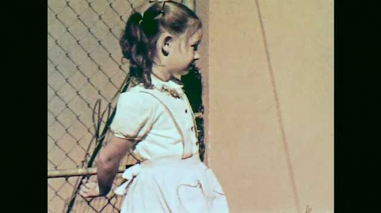 1950s: girl leans against chain link fence gate. girl in red dress dries off feet as boy in sweater spanks back when woman in apron steps from door with socks and shoes.