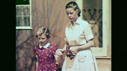 1950s: woman in apron and girl in red dress hold hands, walk across backyard, kneel down and talk. boy in sweater puts sock on bare foot. cat plays with small shoes.