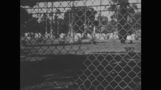 1950s: Chain link fence with graveyard behind. Woman walks in front of sandwich shop.