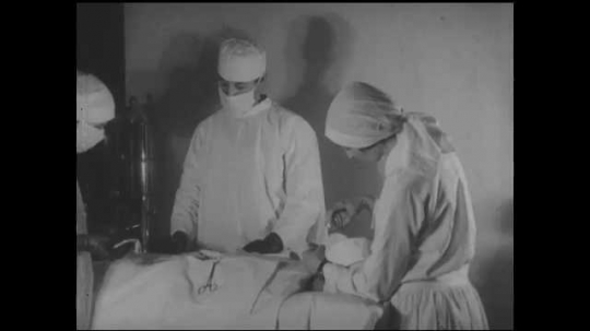 1930s: UNITED STATES: surgeon operates on patient in theatre. Nurse gives gas to patient. Man in wheelchair.