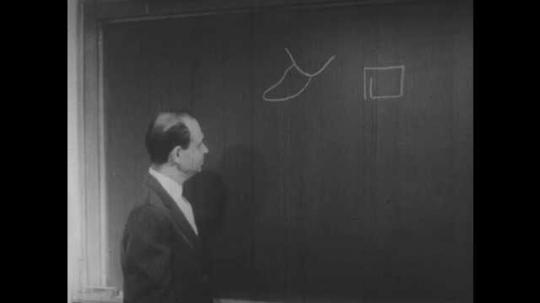 1950s: UNITED STATES: Man writes Roman alphabet on chalk board. Letter A in Roman alphabet. Letter B on chalk board in Roman alphabet