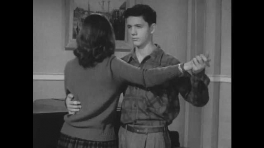1950s: Young man and woman demonstrate a dance position together.
