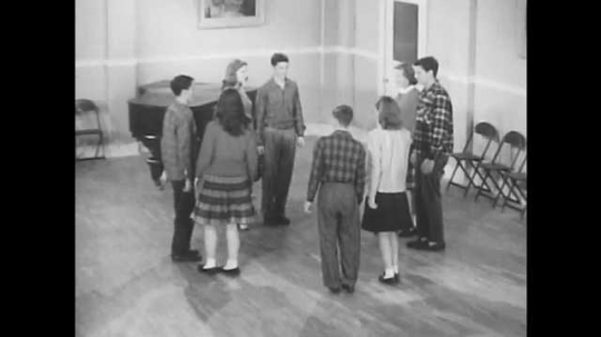 1950s: Four couples stand together to form a square.  Dance partners join hands and walk in a circle.  Couples switch partners.