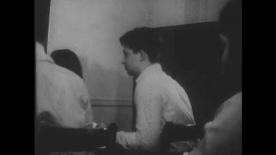 1960s: UNITED STATES:  boy throws paper aero plane in class. Students throw planes in class. Teacher writes on blackboard