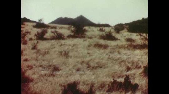 1940s: Dry grassland with mountain in the distance. Water flows over small waterfall in river. Lake.