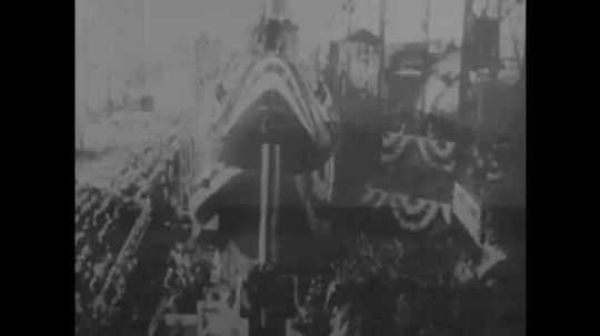 1950s: Hull of submarine in bunting is christened with champagne and launched into ocean. Drawing of Seawolf and Nautilus submarines.  Exterior of GE plant and security for Knolls Atomic Power Lab.
