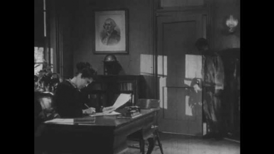1950s: Boy enters office, talks to woman at desk, man enters.